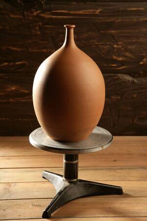potter wheel pottery clay jar vase finished over wood background photo