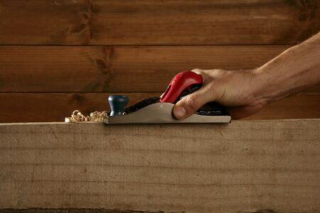 wood planer: carpenter planning wood planer tool man hand wooden background Stock Photo