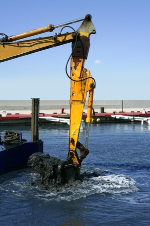 marine dredging digging sea bottom black mud in marina photo