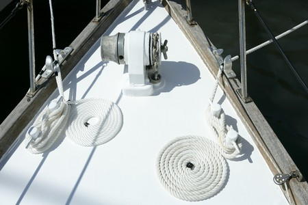 moored: sailboat white bow with bollard and spiral rope moored on port