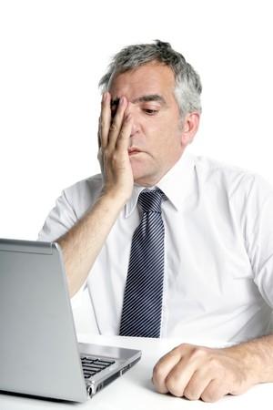 stressed senior businessman gesture working laptop computer white desk photo