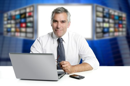 presenter: gray hair tv news screen presenter laptop smiling white desk