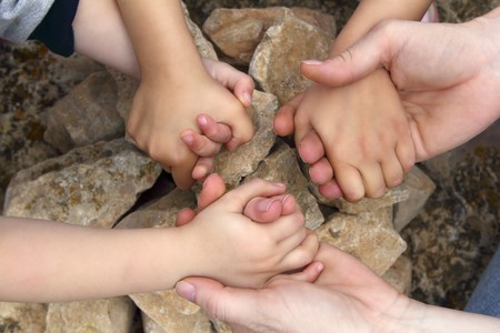 steencirkel: volwassene en chilcren hand in hand rond steen cirkel wensen wens