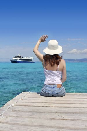 to say: Woman tourist illetas Formentera saying boat goodbye gesture turquoirse sea Stock Photo
