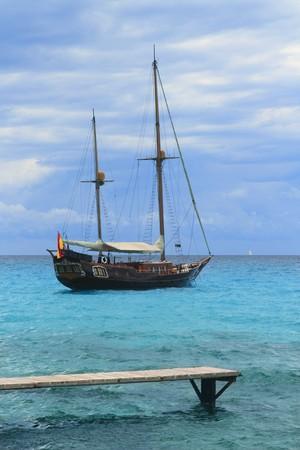 pirates inspired wood sailboat anchored turquoise sea Formentera Stock Photo - 7357202