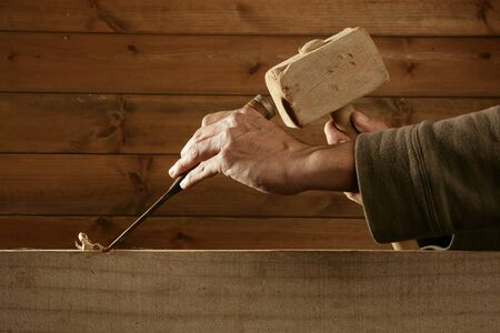 chisel: gouge wood chisel carpenter tool hammer in hand working wooden background Stock Photo