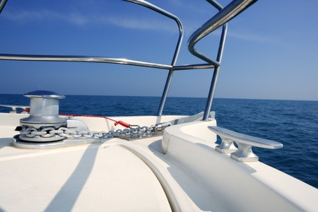 boat bow sailing on blue sea with anchor chain and winch detail photo