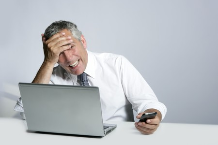 laughing senior businessman computer phone hand gesture on head photo