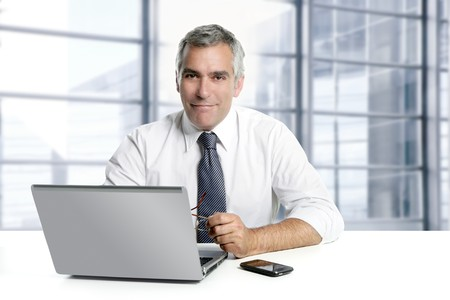businessman senior gray hair working laptop interior modern white office photo