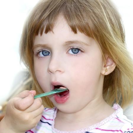 eye cream: blond little girl eating ice cream color spoon portrait