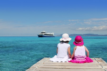 little sisters tourist turquoise sea back in Formentera Stock Photo