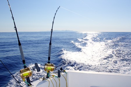charter: Trolling offshore fisherboat rod reels wake sea reflection horizon Stock Photo