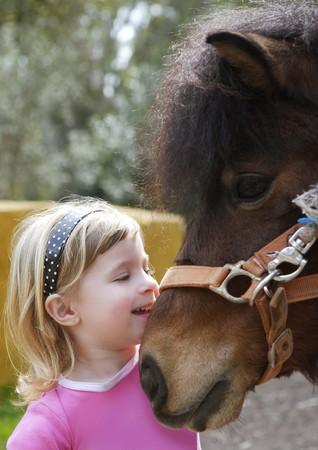 little blond girl loves her pony funny portrait Stock Photo