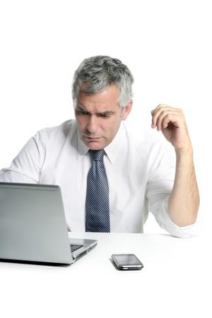 businessman senior gray hair working laptop computer white desk background photo