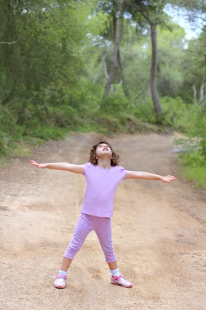 girl in the forest: open hands happy little girl forest truck pine woods park Stock Photo