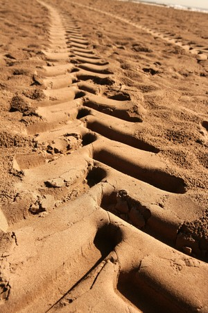 industrial tractor footprint on beach golden sand photo