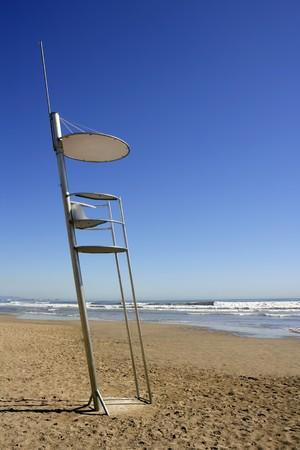 baywatch: Baywatch high chair sand beach in Valencia Spain blue sky Stock Photo