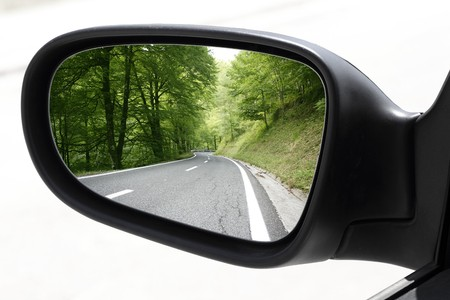 reflection in mirror: rearview car driving mirror view green forest road