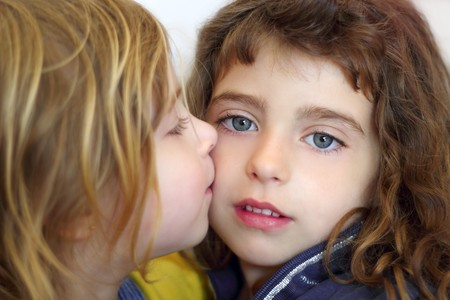 blond little girl kissing her sister blue eyes photo