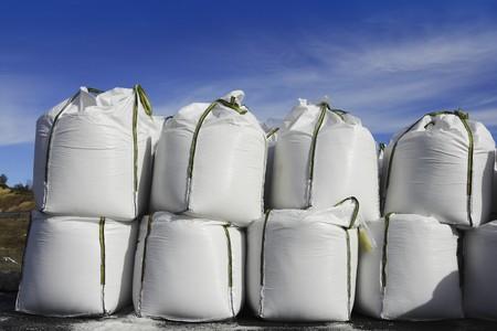 sacks: salt white sacks rows stacked to prevent ice  roads asphalt