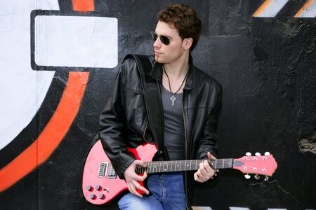 rocker rock star man on black graffiti holding red electric guitar leather jacket photo