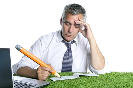 businessman senior sign bank check pensively humor gesture big pencil green grass desk photo