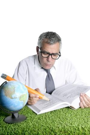 senior student teacher humor glasses world map book big pencil green grass desk photo