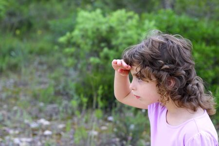 girl in the forest: explorer little girl forest park searching hand in forehead