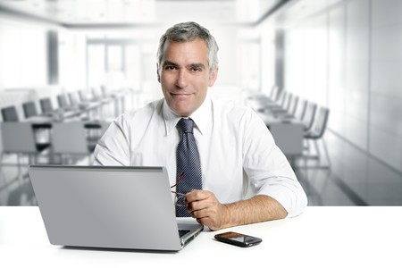 businessman phone: businessman senior gray hair working laptop interior modern white office Stock Photo