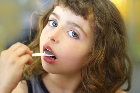 brunette little girl eating  plastic spoon photo