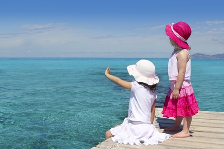 two girls tourist turquoise sea back goodbye boat hand gesture Formentera photo