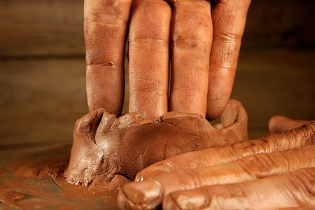 potter: pottery craftmanship red clay potter hands work finger closeup Stock Photo