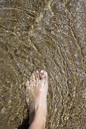 pies masculinos: Playa tur�stica pies caminando sobre la met�fora de las vacaciones de verano de aguas poco profundas de Costa