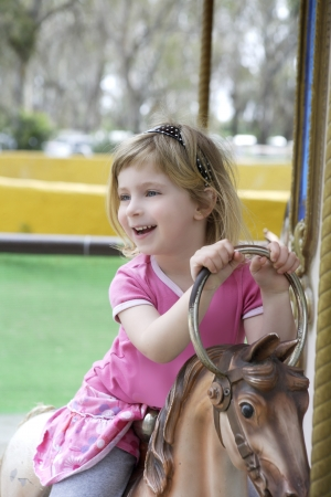 fairground: funny happy gesturing little blond girl playing on horses merry go round