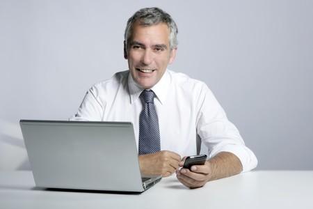happy senior smiling businessman laptop computer mobile phone portrait photo