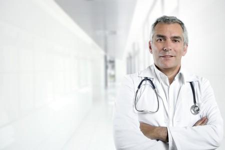 mature male: gray hair expertise handsome senior doctor hospital portrait white corridor