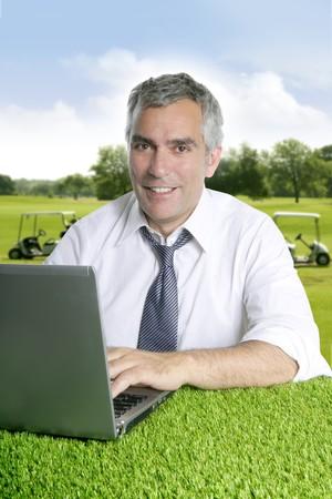 executive courses: senior businessman golf course working computer green grass desk