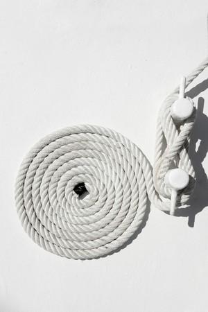bollard: spiral white sea nautical rope on sailboat boat mooring