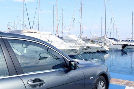 luxury car and yacht sailboats on Spain marina blue mediterranean sea