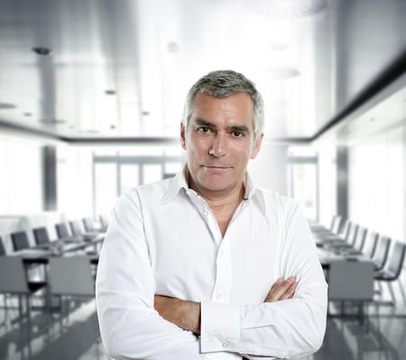 clever: senior expertise gray hair businessman posing interior white modern office