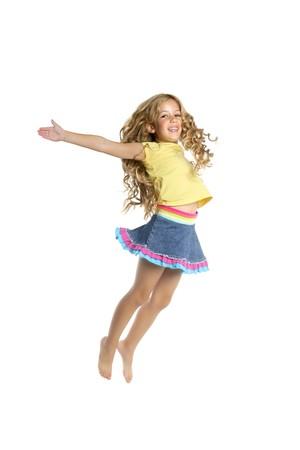 salto largo: Ni�a saltando de fondo de estudio blanco de longitud completa de brazos abiertos