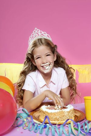 little blond birthday party girleating cake with hands on pink background Stock Photo - 7780998