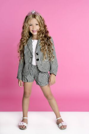Full length little girl stand on pink background at studio photo