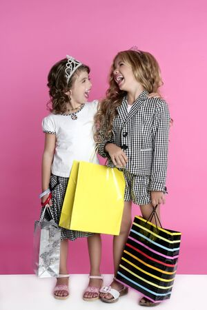 Little shopper humor shopaholic two girls stand full length pink background photo