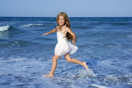 Little girl running beach shore splashing water in blue sea photo