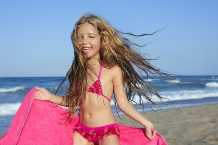 beach towel: Beach little girl playing pink towel and wind in blue sea Stock Photo