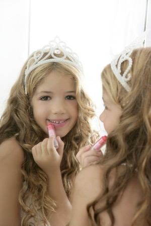 princess crown: princess little girl painting makeup lipstick on the mirror Stock Photo