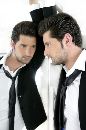 enticement: Handsome narcissistic suit proud young man looking himself in the mirror  Stock Photo