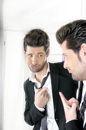 Traje de guapo orgulloso joven ensaya un juego humor gracioso brillantes en un espejo