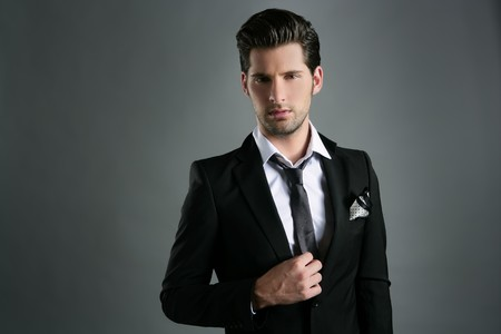 male model: Fashion young businessman black suit casual tie on gray background